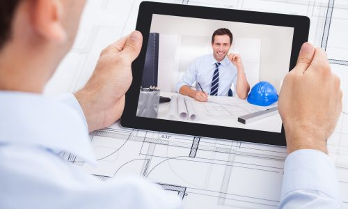 Cropped image of male architect video conferencing with colleague through digital tablet in office
